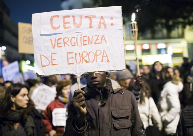 An immigrant holds a placard during a protest for the death of at least 9 immigrants in Spain's North African enclave of Ceuta a week ago while they were trying to enter Spain, in Madrid February 12. The placard reads ''Ceuta: shame of Europe''. Picture taken February 12, 2014. REUTERS/Juan Medina