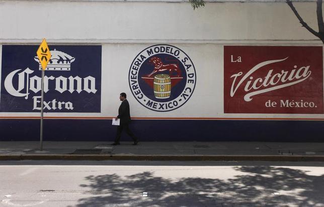 A man walks past the logo of Grupo Modelo in Mexico City July 16, 2013. REUTERS/Edgard Garrido