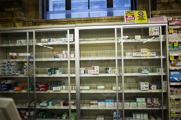 Near empty cigarette shelves are seen at a CVS store in New York February 4, 2014. REUTERS/Eric Thayer