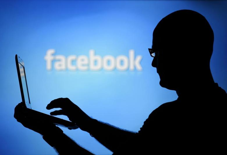 A man is silhouetted against a video screen with an Facebook logo as he poses with an Dell laptop in this photo illustration taken in the central Bosnian town of Zenica, August 14, 2013. REUTERS/Dado Ruvic