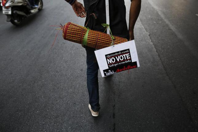 An anti-government protester carrying a ''No Vote'' sign follows others moving from one protest camp to another in Bangkok February 3, 2014 file photo. REUTERS/Damir Sagolj