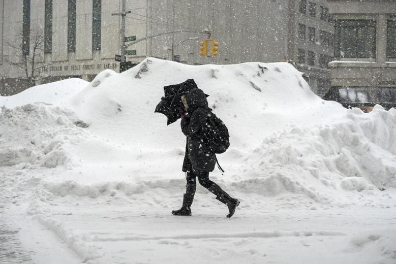 A woman uses an umbrella to shelter from snow flurries as she walks along a street in the Manhattan borough of New York February 13, 2014. REUTERS/Zoran Milich