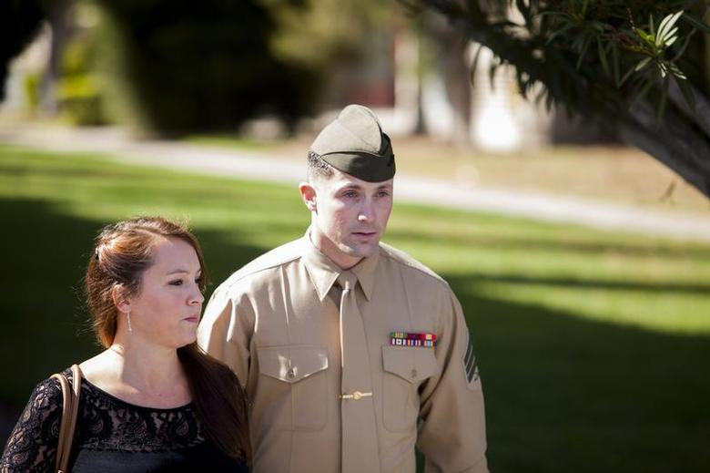United States Marine Sergeant Lawrence Hutchins III departs from his arraignment hearing with his wife Reyna Hutchins at Camp Pendelton, California February 13, 2014. Hutchins, who was found guilty of murder in the 2006 death of an Iraqi civilian, only to have his conviction overturned, will face a retrial on the same charges. REUTERS/Sam Hodgson