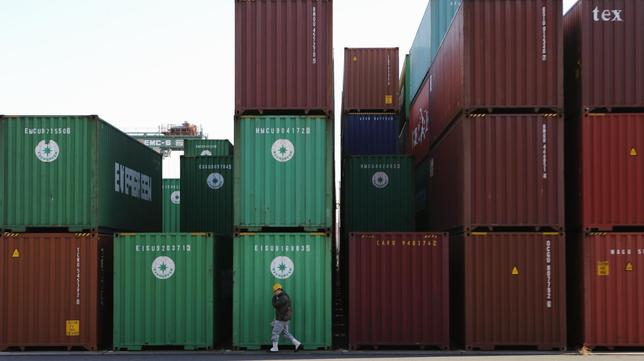 A worker walks in a container area at a port in Tokyo January 27, 2014. REUTERS/Toru Hanai