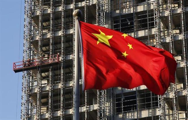2月14日、報道によると中国の「影の銀行(シャドーバンキング)」取引のデフォルト危機で注目される経営難の石炭会社、山西聯盛能源に対し、国内の信託会社6社が総額50億元(8億2460万ドル)以上を融資していたことが分かり、新たなデフォルト懸念が浮上している。写真は北京の建築現場に掲げられた中国国旗。昨年11月撮影(2014年 ロイター/Kim Kyung-Hoon)