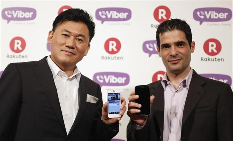 Chairman and Chief Executive of e-commerce operator Rakuten Inc Hiroshi Mikitani (L) and Viber Media Chief Executive Talmon Marco hold their smartphones as they pose during a news conference in Tokyo February 14, 2014. REUTERS/Yuya Shino