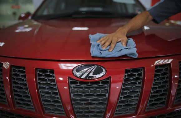 A showroom attendant cleans a Mahindra XUV500 car inside the company's showroom in Mumbai May 30, 2013. REUTERS/Danish Siddiqui/Files