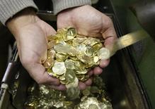 Работник монетного двора держит десятирублевые монеты в Санкт-Петербурге 9 февраля 2010 года. Рубль торгуется в минусе на пятничной биржевой сессии, обновив абсолютный минимум против евро и бивалютной корзины во многом за счет покупок валюты иностранными участниками, игнорируя стабильно высокие цены на нефть и февральский налоговый период, стартующий в понедельник. REUTERS/Alexander Demianchuk