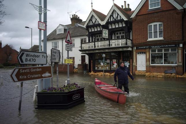 A man pushes his boat through the flooded central square in the village of Datchet in Berkshire, southern England, in this February 12, 2014 file photo. REUTERS/Kieran Doherty/Files