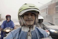 Покрытый пеплом мужчина едет на мопеде в Йогьякарте 14 февраля 2014 года. Власти Индонезии эвакуировали в пятницу более 100.000 человек из-за извержения вулкана на густонаселенном острове Ява. REUTERS/Dwi Oblo