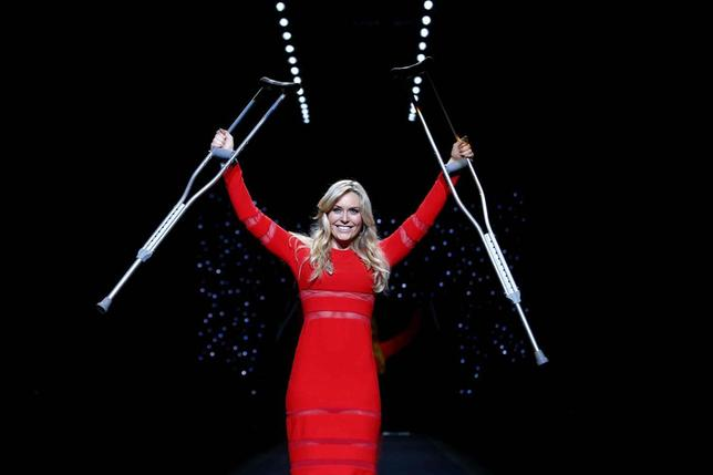 Olympic downhill champion Lindsey Vonn raises her crutches as she presents a creation by Cynthia Rowley for the The Heart Truth Fall 2014 collection during New York Fashion Week February 6, 2014. REUTERS/Joshua Lott