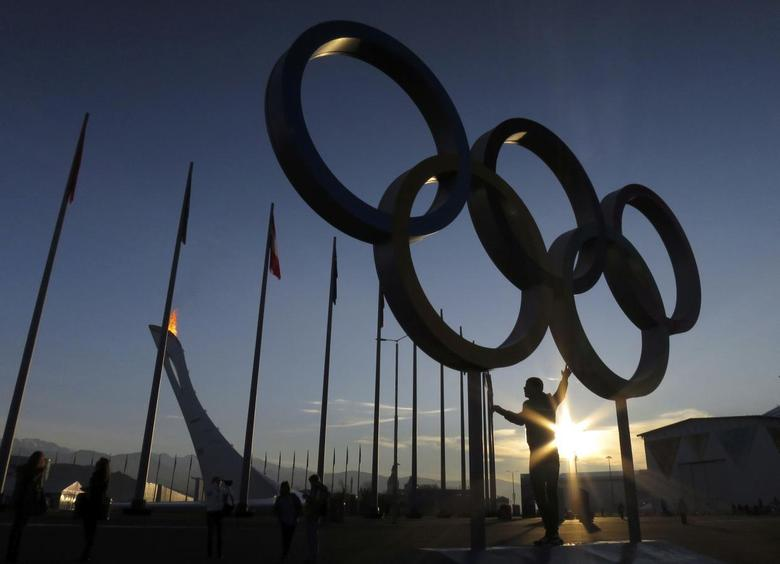 A person poses under a set of Olympic rings as the sun rises on the Olympic Park at the 2014 Sochi Winter Olympics, February 12, 2014. REUTERS/Gary Hershorn