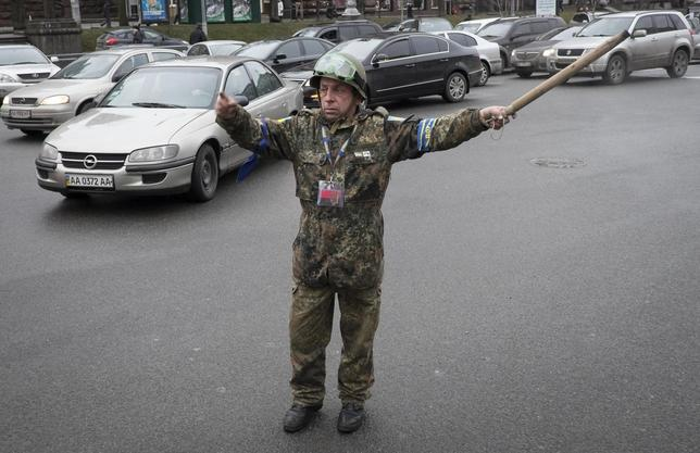 An anti-government protester works on a road near the barricades in Kiev February 13, 2014. REUTERS/Gleb Garanich