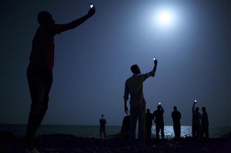 John Stanmeyer, a U.S. photographer working for VII agency on assignment for National Geographic, won the World Press Photo of the Year 2013 contest with this picture of African migrants on the shore of Djibouti city at night taken February 26, 2013. REUTERS/John Stanmeyer/World Press Photo Handout via Reuters