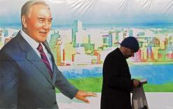 """Мужчина читает книгу на фоне плаката с президентом Казахстана Нурсултана Назарбаева в Алма-Ате 28 ноября 2012 года. Назарбаев приказал распечатать копящий доходы от экспорта нефти стратегический Нацфонд, чтобы поддержать экономику на фоне 19-процентной девальвации тенге, и велел разгрузить банки от бремени """"плохих"""" кредитов. REUTERS/Shamil Zhumatov"""