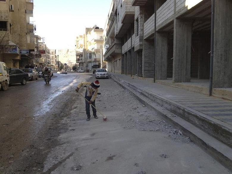 A boy cleans debris near buildings damaged by what activists said were shelling by forces loyal to President Bashar al-Assad, at Yabroud, near Damascus January 3, 2013. REUTERS/Shaam News Network/Handout