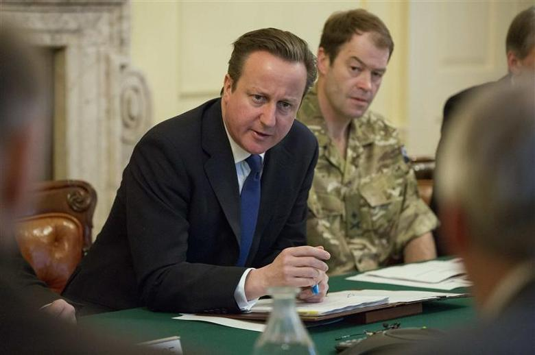 Britain's Prime Minister David Cameron (L) speaks during a Cobra meeting at Number 10 Downing Street in London February 12, 2014. REUTERS/Neil Hall