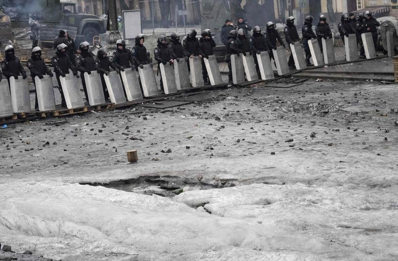 Riot police stand guard near barricades built at the site of recent clashes with anti-government protesters in Kiev February 13, 2014. REUTERS/Gleb Garanich