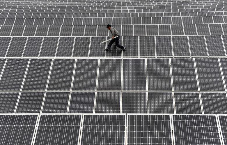An employee walks on solar panels at a solar power plant in Aksu, Xinjiang Uyghur Autonomous Region May 18, 2012. REUTERS/Stringer