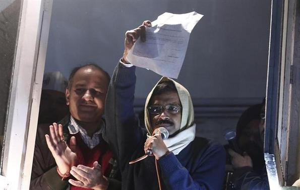 Delhi's Chief Minister Arvind Kejriwal, chief of the Aam Aadmi Party (AAP), shows his resignation to his supporters while addressing them from his party headquarters in New Delhi February 14, 2014. REUTERS/Adnan Abidi
