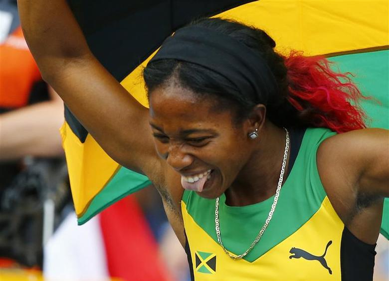 Shelly-Ann Fraser-Pryce of Jamaica holds her national flag after winning the women's 4x100 metres relay final during the IAAF World Athletics Championships at the Luzhniki stadium in Moscow August 18, 2013. REUTERS/Dominic Ebenbichler
