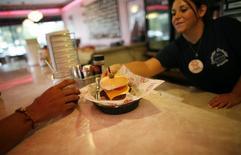 Una empleada sirve una hamburguesa en un restaurante de la cadena Cheeburger Cheeburger en Coral Spring, EEUU, jul 28 2008. Economistas recortaron sus pronósticos del crecimiento económico de Estados Unidos en el primer trimestre del año, con una expansión del empleo que seguiría siendo tenue, pero esperan que el ritmo de la actividad se intensifique en el segundo trimestre. REUTERS/Carlos Barria