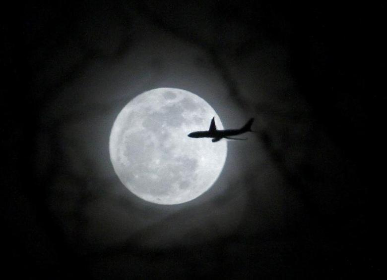 A plane passes in front of a full moon over New York City February 17, 2011. REUTERS/Eric Thayer