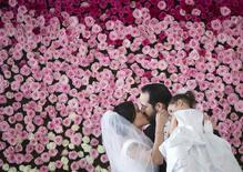 Brendan Goldblatt holds daughter Victoria as he kisses wife Maria Vasquez after getting married at the Empire State Building in the Manhattan borough of New York February 14, 2014. REUTERS/Carlo Allegri