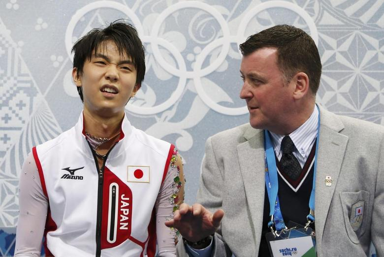 Japan's Yuzuru Hanyu reacts with coach Brian Orser in the ''kiss and cry'' area during the Figure Skating Men's Free Skating Program at the Sochi 2014 Winter Olympics, February 14, 2014. REUTERS/Lucy Nicholson