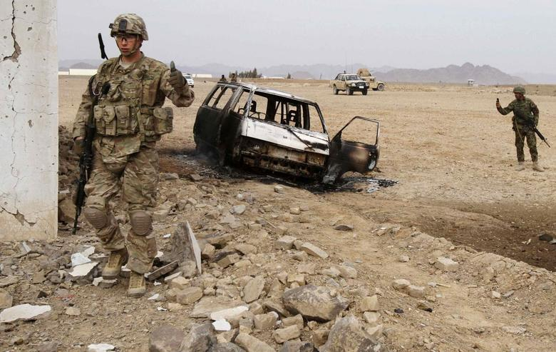 A U.S. soldier stands at the site of a suicide attack on a NATO base in Zhari, west of Kandahar province, January 20, 2014. REUTERS/Ahmad Nadeem