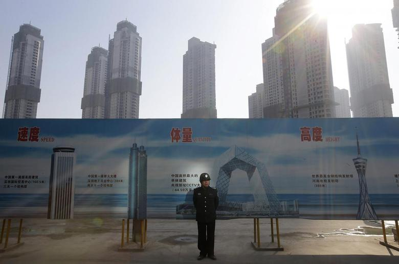 A security guard stands next to an advertising board in front of a residential compound under construction in Wuhan, Hubei province January 21, 2014. REUTERS/Stringer