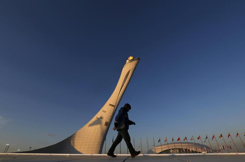 A workman walks on the cauldron at sunrise at the Olympic Park during the 2014 Sochi Winter Olympics, February 15, 2014. REUTERS/Gary Hershorn