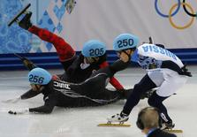 Canada's Charles Hamelin (back) and Eduardo Alvarez of the U.S. (front) fall as Russia's Victor An (R) skates past during the men's 1,000 metres short track speed skating quarter-finals race at the Iceberg Skating Palace at the Sochi 2014 Winter Olympic Games February 15, 2014. REUTERS/Eric Gaillard