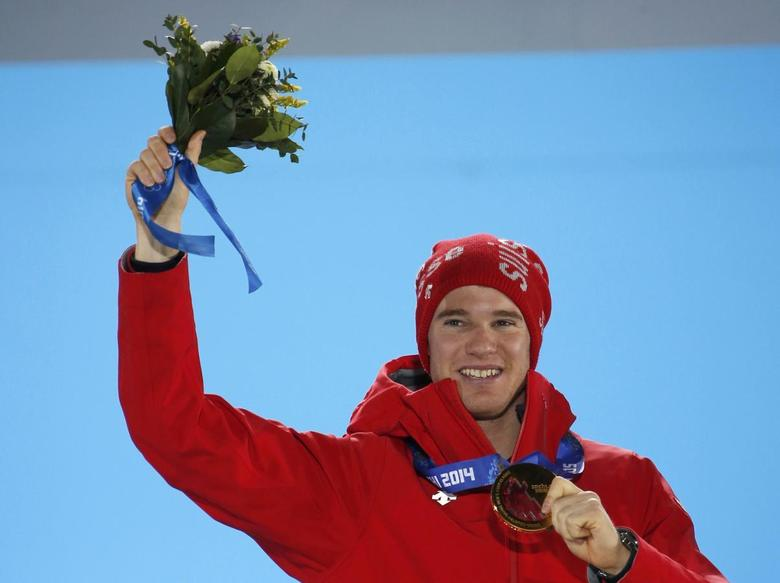 Gold medallist Switzerland's Dario Cologna poses during the victory ceremony for the men's cross-country 15km classic event at the 2014 Sochi Winter Olympics February 14, 2014. REUTERS/Eric Gaillard