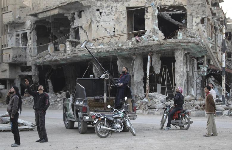 Free Syrian Army fighters and civilians look at the sky as they stand past damaged buildings in Deir al-Zor, eastern Syria February 14, 2014. REUTERS/Khalil Ashawi