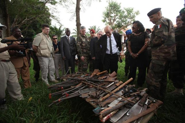 French Defense Minister Jean Yves-Le Drian (C) and Central African Republic's interim President Catherine Samba Panza (2nd R) look at seized weapons during his visit to Mbaiki, about 105 km (65 miles) away from Bangui, February 12, 2014. Picture taken February 12, 2014. REUTERS/Media Coulibaly