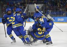 Sweden's women's ice hockey players celebrate after defeating Finland in their women's ice hockey playoffs quarter-final game at the Sochi 2014 Winter Olympic Games February 15, 2014. REUTERS/Brian Snyder