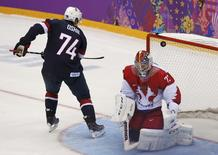 Team USA's T.J. Oshie scores on the team's fifth shootout attempt against Russia's goalie Sergei Bobrovski during their men's preliminary round ice hockey game at the Sochi 2014 Winter Olympic Games February 15, 2014. REUTERS/Grigory Dukor