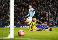 Manchester City's Stevan Jovetic (C) scores a goal as Chelsea's Petr Cech (L) and Cesar Azpilicueta react during their English FA Cup fifth round soccer match at the Etihad Stadium in Manchester, northern England February 15, 2014. REUTERS/Darren Staples