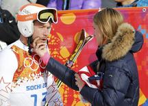 Bode Miller (L) of the U.S. cries next to his wife Morgan Beck in the mixed zone after finishing in the men's alpine skiing Super-G competition during the 2014 Sochi Winter Olympics at the Rosa Khutor Alpine Cente February 16, 2014. REUTERS/Leonhard Foeger