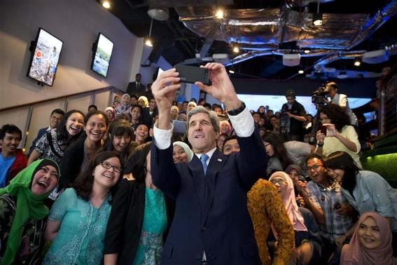 U.S. Secretary of State John Kerry (C) takes a selfie with a group of students before delivering a speech on climate change in Jakarta February 16, 2014. REUTERS/Evan Vucci/Pool