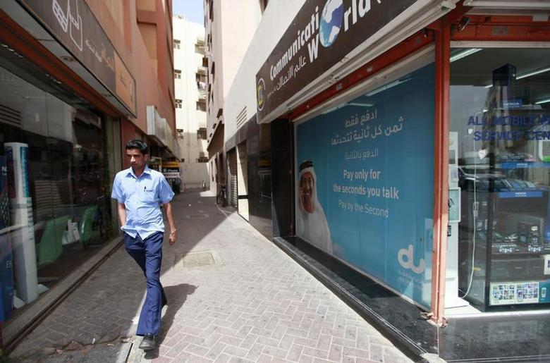 A man walks past a Du telecommunications advertisement in Deira in Dubai March 12, 2012. REUTERS/Jumana El Heloueh