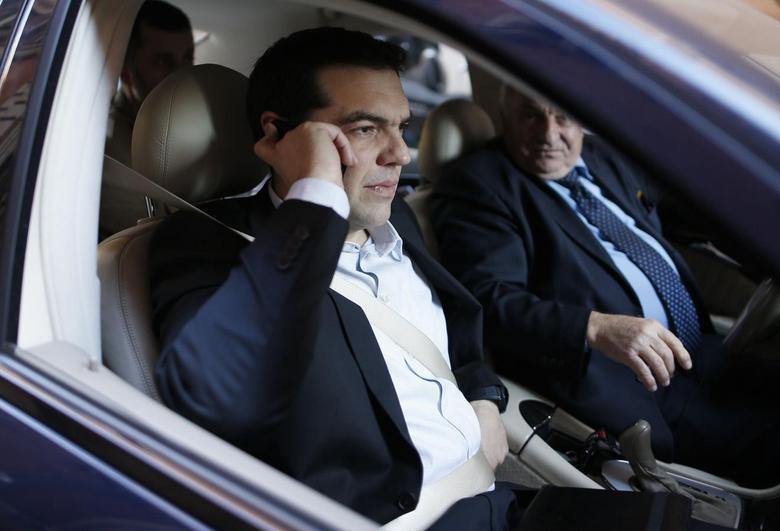 Greek radical left unified party President Alexis Tsipras (L) talks on his mobile phone as he arrives for a news conference for foreign press during his visit in Rome February 7, 2014. REUTERS/Alessandro Bianchi