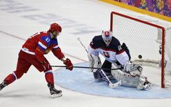 Russia's Alexander Radulov (L) scores on Slovakia's goalie Jan Laco on his team's first shootout attempt during their men's preliminary round ice hockey game at the Sochi 2014 Winter Olympic Games February 16, 2014. REUTERS/Grigory Dukor