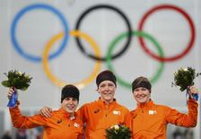 (L to R) Second-placed Ireen Wust, first-placed Jorien ter Mors and third-placed Lotte Van Beek, all of the Netherlands, celebrate on the podium during the flower ceremony for the women's 1,500 metres speed skating event at the Adler Arena during the 2014 Sochi Winter Olympics, February 16, 2014. REUTERS/Issei Kato