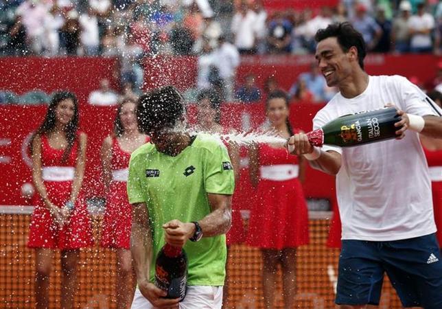 Fabio Fognini (R) of Italy sprays champagne over David Ferrer of Spain after Ferrer defeated him in their men's singles final tennis match at the ATP Buenos Aires Open, February 16, 2014. REUTERS/Marcos Brindicci