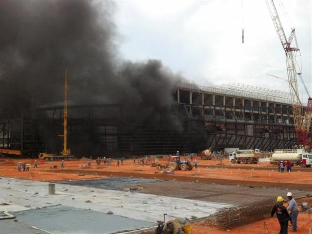 Smoke billows from the partially-constructed Arena Pantanal soccer stadium, projected to host 2014 World Cup matches, from a fire in the base of the structure, in Cuiaba October 25, 2013. REUTERS/Raphael Joanucci/Files