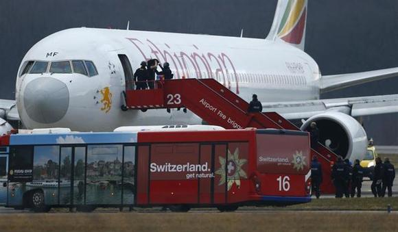 Police officers help a passenger disembark hijacked Ethiopian Airlines flight ET 702 at Cointrin airport in Geneva February 17, 2014. REUTERS/Denis Balibouse