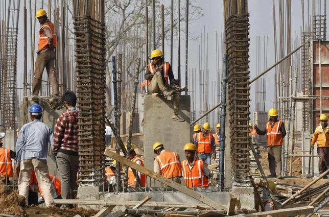 Labourers work at the construction site of an educational institute in Gujarat December 21, 2013. benefits. REUTERS/Amit Dave/Files