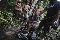 Munduruku Indian warriors stand guard over an illegal gold miner who was detained by a group of warriors searching out illegal gold mines and miners in their territory near the Caburua river, a tributary of the Tapajos and Amazon rivers in western Para state January 20, 2014. REUTERS/Lunae Parracho